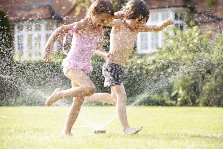 Kinder springen durch Wasser