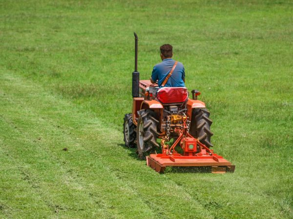 a man on mower cutting grass in football field