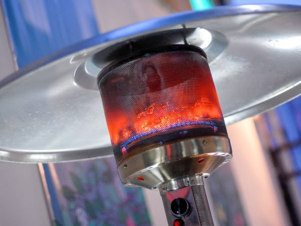 Design stainless steel metal gas burning indoor patio heater with blurred enteriour background